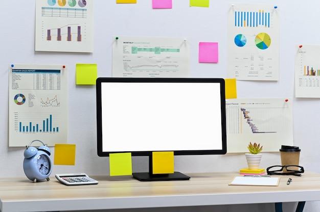 Pusty ekran komputera z pustą tablicą do pisania, zegarem i kalkulatorem z materiałami biurowymi, kubkiem do zabrania na biurko, wykresem danych i papierem do notatek na ścianie biura.