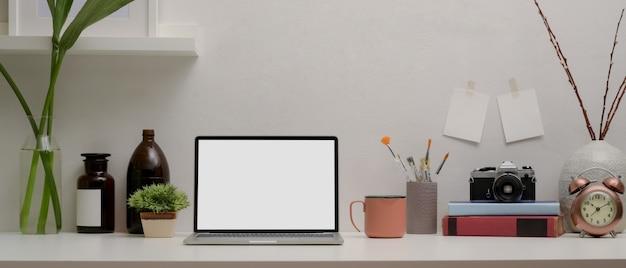 Pusty ekran laptopa na białym biurku z materiałami i dekoracjami w pokoju biurowym w domu
