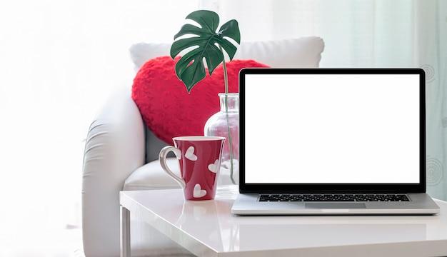 Pusty ekran laptopa na białym stole w salonie