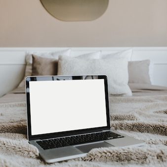 Pusty ekran laptopa na łóżku z poduszkami przed beżową ścianą. skopiuj szablon makiety przestrzeni. praca w domu koncepcja dla mediów społecznościowych, strony internetowej, bloga.