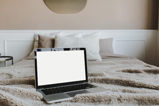 Pusty ekran laptopa na łóżku z poduszkami przed beżową ścianą