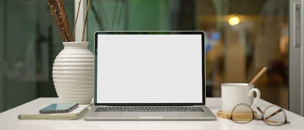 Pusty ekran laptopa na stole roboczym z kubkiem, smartfonem, materiałami eksploatacyjnymi i dekoracją w szklanym pokoju biurowym