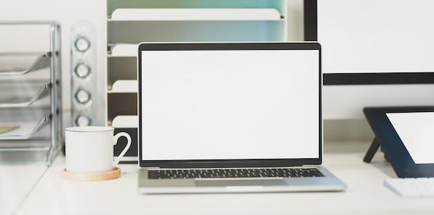 Pusty ekran laptopa w wygodnym miejscu pracy z artykułami biurowymi i filiżanką kawy