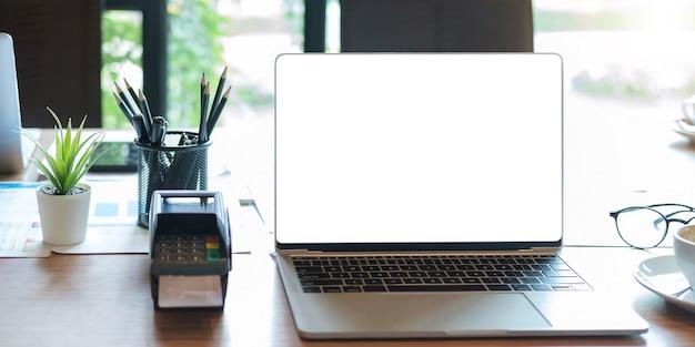 Pusty ekran laptopa z maszyną edc na stole w kawiarni