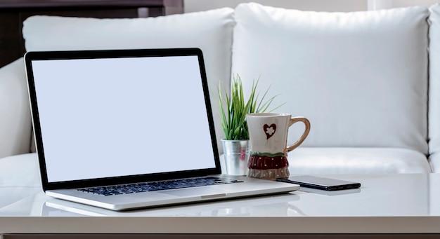 Pusty ekran laptopa ze smartfonem, kubkiem i rośliną doniczkową na biały drewniany blat w salonie.
