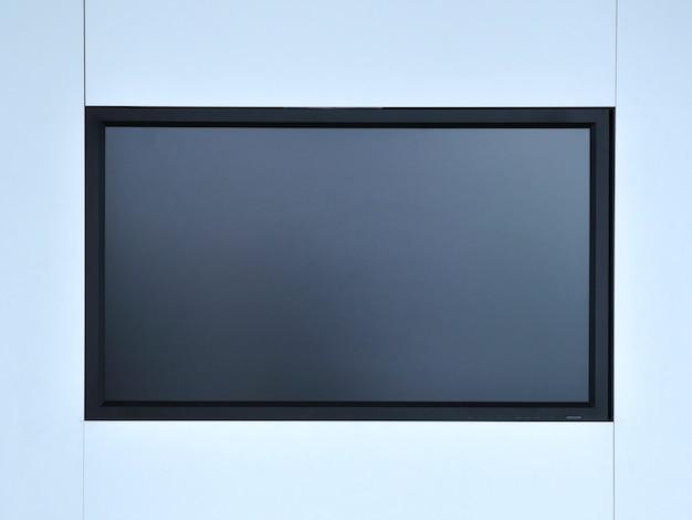 Pusty ekran monitora zawieszony na białej ścianie