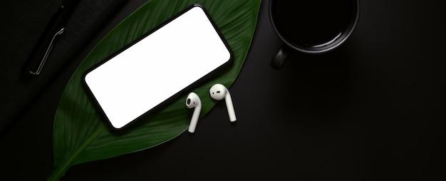 Pusty ekran smartfona, bezprzewodowe słuchawki nad liściem i filiżankę kawy na ciemnym tle