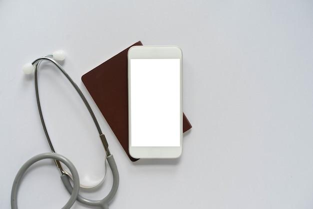 Pusty ekran smartfona do projektowania leżał z paszportem i stetoskopem do koncepcji kontroli zdrowia