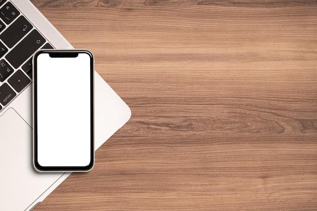 Pusty ekran smartfona i laptopa do makiety na tle piękne drewniane biurko.