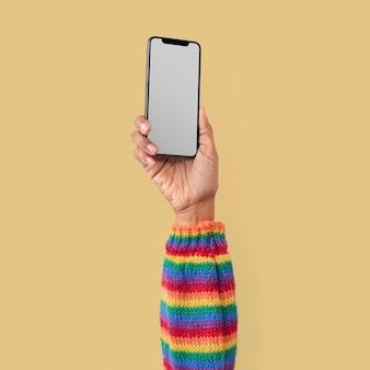 Pusty ekran smartfona na białym tle w studio z podniesioną ręką