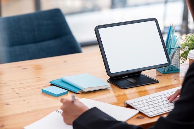Pusty ekran tabletu na stojaku na drewnianym stole z miejsca na kopię. przycięte strzał businesswoman ręce pracy na komputerze.