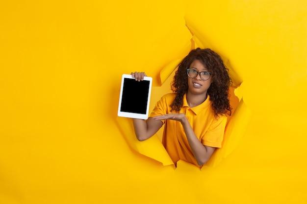 Pusty ekran tabletu. wesoła afro-młoda kobieta w rozdartym tle żółtego papieru, emocjonalna, ekspresyjna. przełamanie, przełom. pojęcie ludzkich emocji, wyraz twarzy, sprzedaż, reklama.