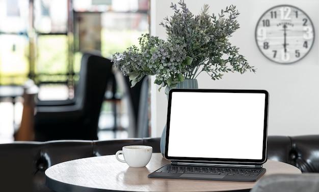 Pusty ekran tabletu z klawiaturą na stole w komfortowym pokoju.