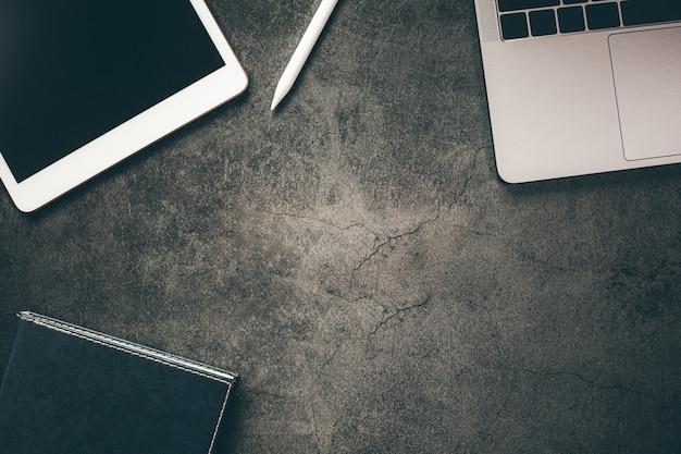 Pusty ekran tabletu z notatnikiem na czarnym tle stołu
