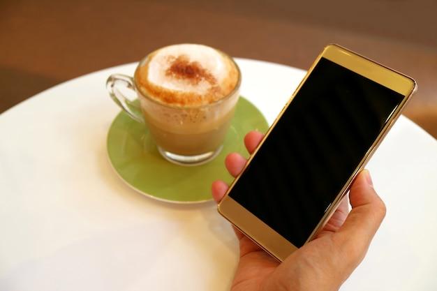 Pusty ekran telefonu komórkowego w ręku z kawą cappuccino na białym okrągłym stole