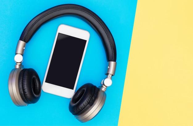 Pusty ekran telefonu komórkowego wewnątrz złotych słuchawek