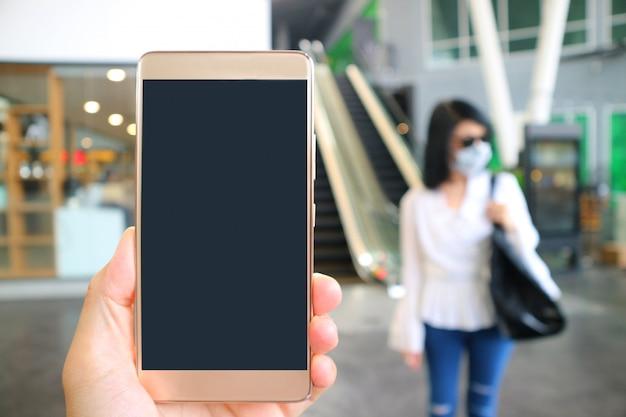 Pusty ekran telefonu komórkowego z rozmytą kobietą noszenie maski