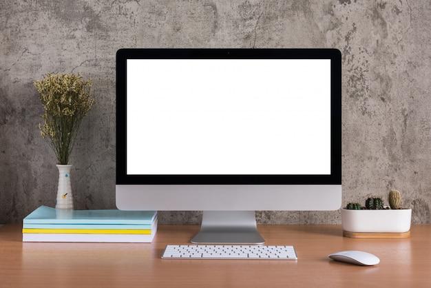 Pusty ekran wszystkiego w jednym komputerze z suchymi kwiatami, książkami i wazonem z kaktusami