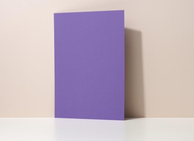 Pusty fioletowy tekturowy arkusz papieru z cieniem na białym stole. szablon ulotki, ogłoszenia