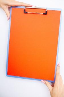 Pusty folder z czerwonym papierem. podaj ten folder i pióro