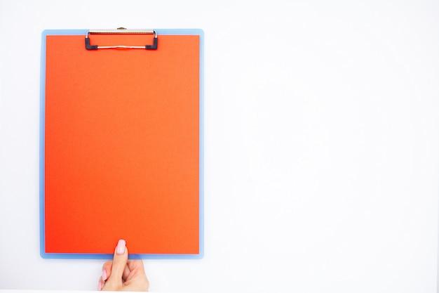 Pusty folder z czerwonym papierem. wręcza ten mienie falcówkę i pióro na białym tle. copyspace.