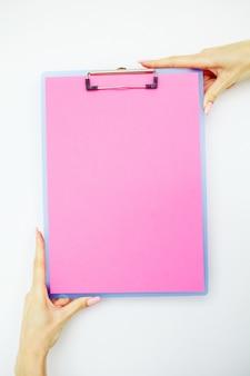 Pusty folder z różowym papierem. ręka, która trzyma folder i uchwyt na białym tle.