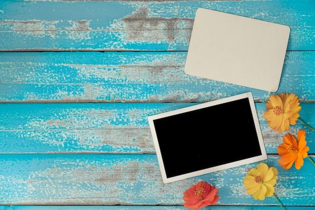 Pusty fotografia ramy album z kwiatem na starym błękitnym drewnianym tle