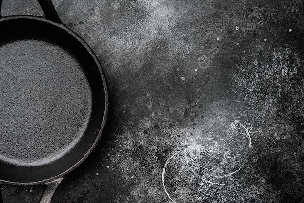 Pusty garnek do gotowania z kopią miejsca na tekst lub jedzenie z kopią miejsca na tekst lub jedzenie, widok z góry płasko leżał, na tle czarnego ciemnego kamiennego stołu