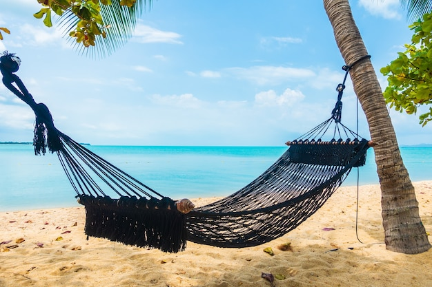 Pusty hamak huśtawka wokół plaży, oceanu morskiego z białą chmurą, błękitnym niebem na wakacje w podróży
