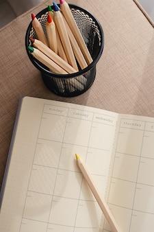 Pusty i pusty kalendarz i dziennik leżące otwarte, oglądane z góry, obok ołówka.
