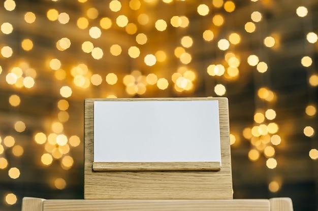 Pusty kalendarz - pamiętnik na dębowej podstawce białej karty,. przeciw bokeh girlandy gwiazd.