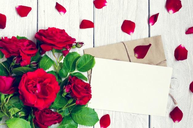 Pusty kartka z pozdrowieniami i koperta z czerwonych róż kwiatami i płatkami