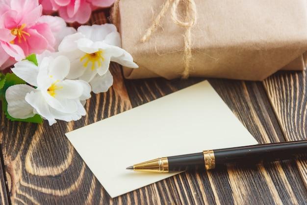 Pusty kartka z pozdrowieniami z kwiatu bukietem na drewnianym tle