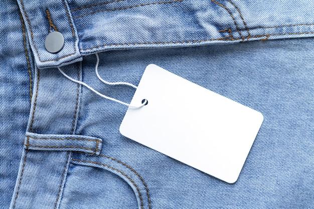 Pusty kartonowy tag lub etykieta z liną na tle ubrania dżinsów