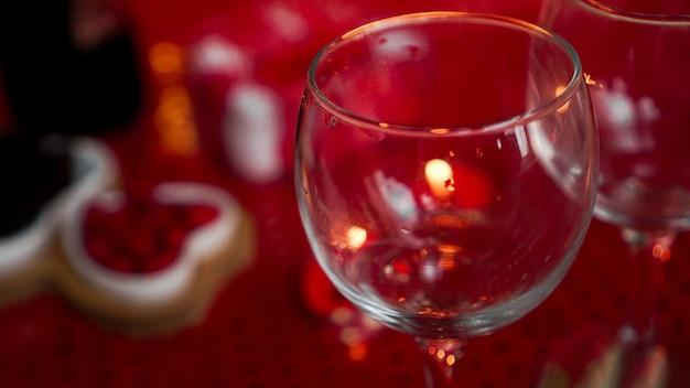 Pusty kieliszek do wina na kolację miłości. świece na walentynki, stół z świątecznym czerwonym tłem.