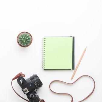 Pusty kolor zielony notebooka i aparat na bia? ym tle, lato koncepcji? ycia