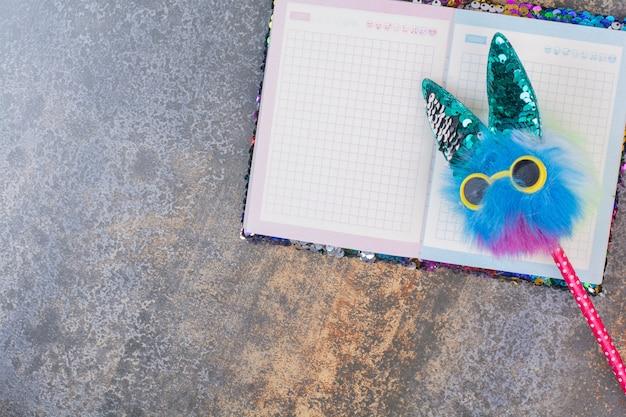 Pusty kolorowy notatnik z zabawnym ołówkiem na marmurowej przestrzeni.