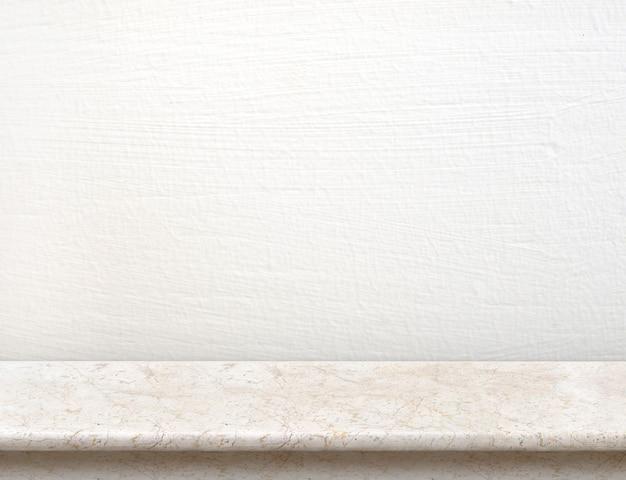 Pusty kremowy blat marmurowy z białą betonową ścianą