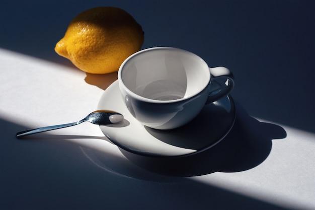 Pusty kubek na herbatę lub kawę z cytryną, porannymi światłami i cieniami