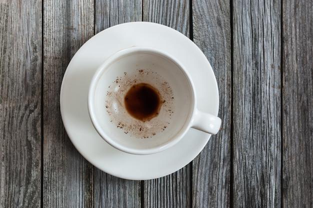 Pusty kubek z resztkami kawy na drewnianym stole, zbliżenie