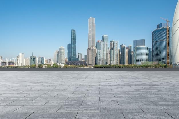 Pusty kwadratowy teren i budynki miejskie w tle