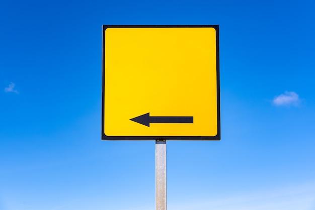 Pusty kwadratowy żółty znak drogowy ze strzałką, który ma zawierać tekst.