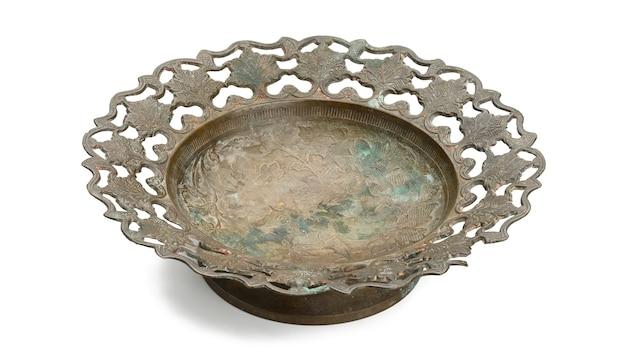 Pusty miedziany okrągły starodawny talerz na białym tle na białym tle, danie owocowe. widok z góry
