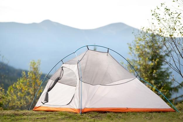 Pusty namiot kempingowy stojący na kempingu z widokiem na majestatyczne szczyty wysokich gór w oddali.