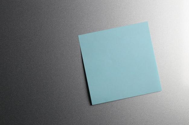 Pusty niebieski arkusz papieru na drzwiach lodówki do projektowania i wprowadzania tekstu.
