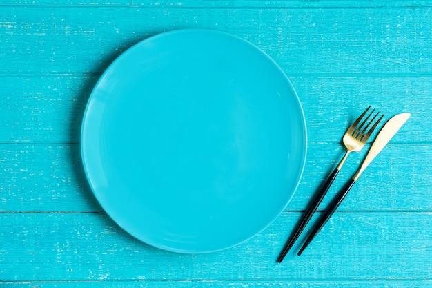 Pusty niebieski ceramiczny okrągły talerz z nożem i widelcem na niebieskim drewnianym stole.
