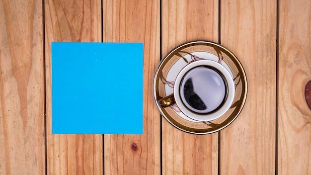 Pusty niebieski papier do cytatów z kawą na drewnianym stole