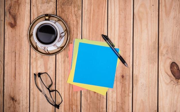 Pusty niebieski papier do cytatów z okularami, kawą i długopisem na drewnianym stole
