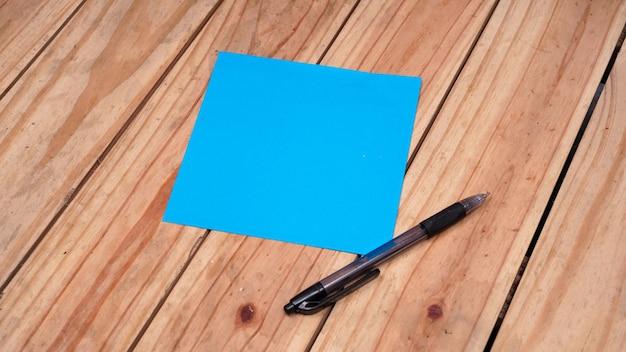 Pusty niebieski papier do cytatów z piórem na drewnianym stole