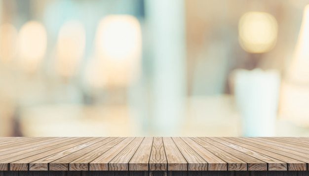 Pusty nieociosany drewniany deska stół i zamazany miękkiego światła stół w restauraci